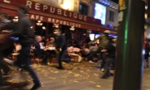People run after hearing what is believed to be explosions or gun shots in Paris on 13 November.