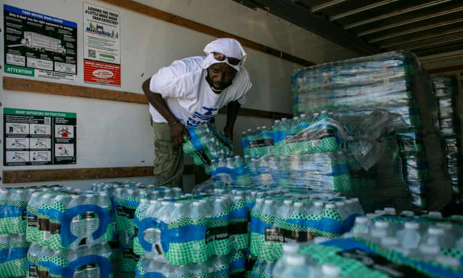 A volunteer hands out water to residents in Benton Harbor, 10 September 2021.