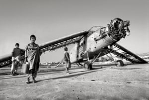 Boys play near a destroyed plane in Kabul, Afghanistan, May 2000.