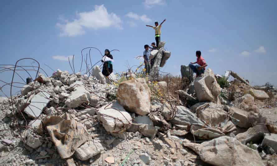 Palestinian children on 7 July 2015 in the village of Khuzaa, east of Khan Yunis in the Gaza Strip, play in the rubble of houses destroyed a year earlier.