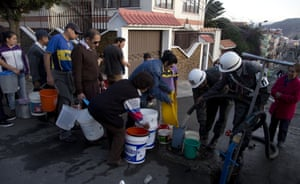Military police distribute water to residents, on a street in La Paz