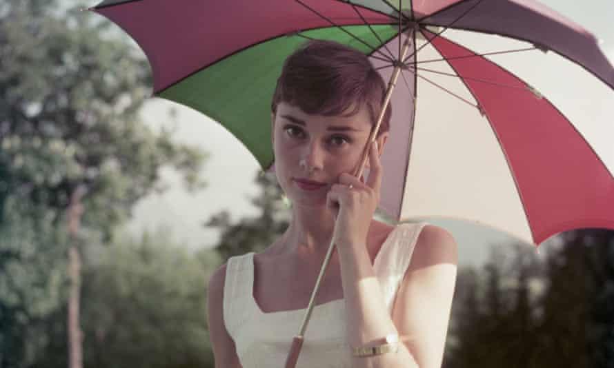 Audrey Hepburn posing with an umbrella in 1955.
