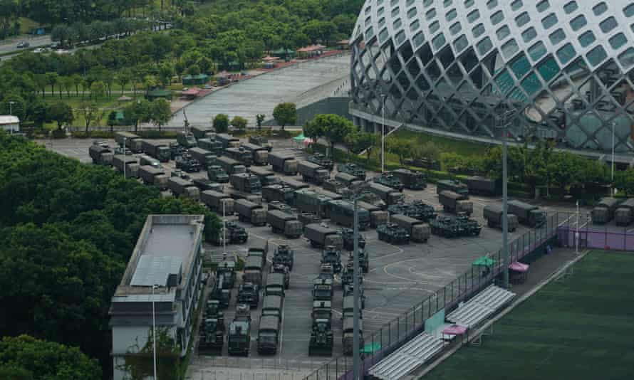 Chinese armoured vehicles and troop trucks parked outside the Shenzhen Bay Stadium on Thursday.