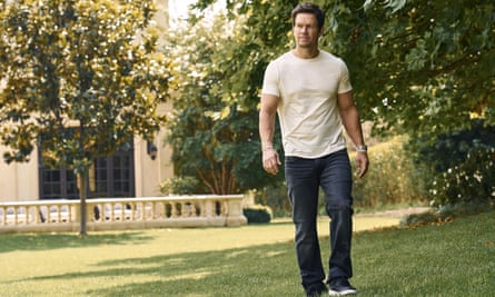 Mark Wahlberg in jeans and T-shirt walking across his garden with trees and his home in the background