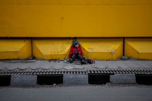 A young shoe shiner waits for customers alongside a street in Kabul.