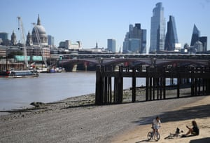 People relax on the banks of the Thames in London