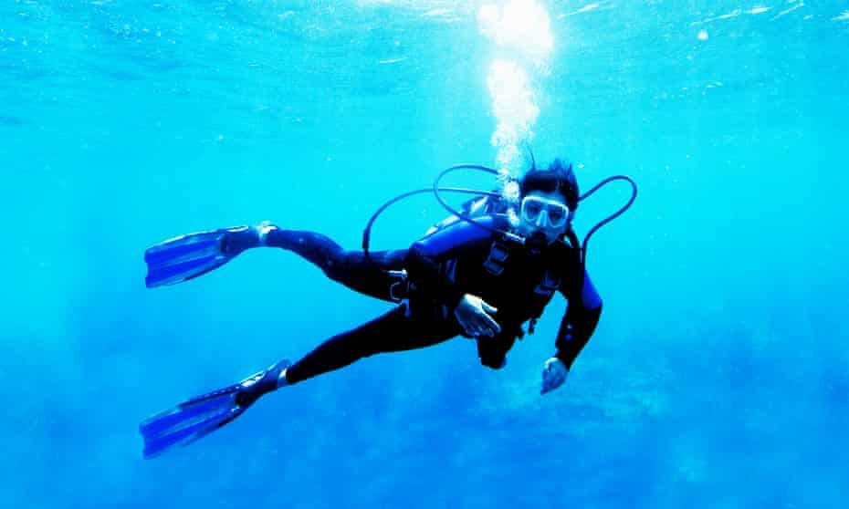 Woman scuba diver in blue ocean.
