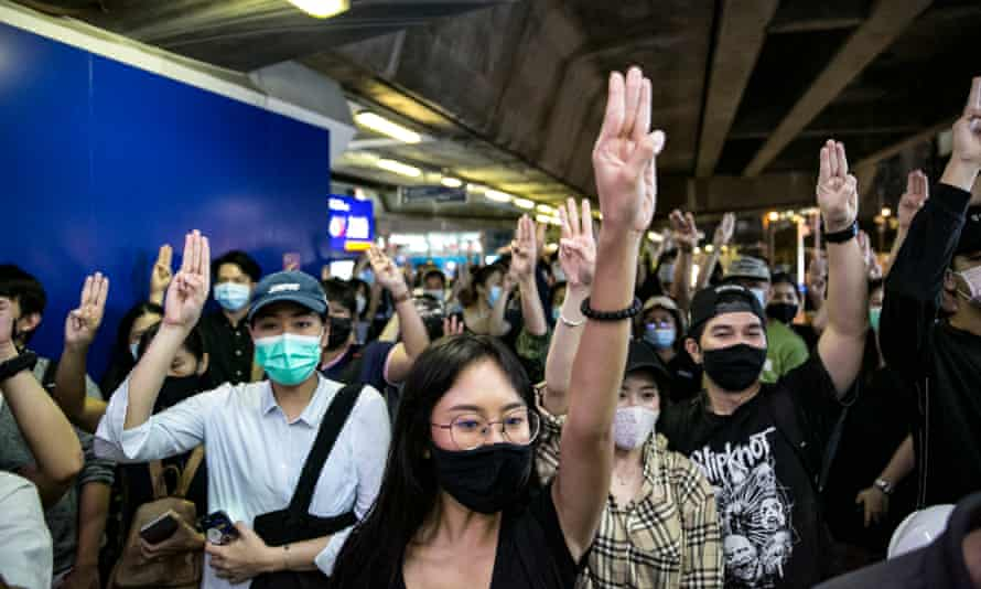Pro-democracy protesters give the three-finger salute at the Asok BTS skytrain station on Tuesday in Bangkok, Thailand.