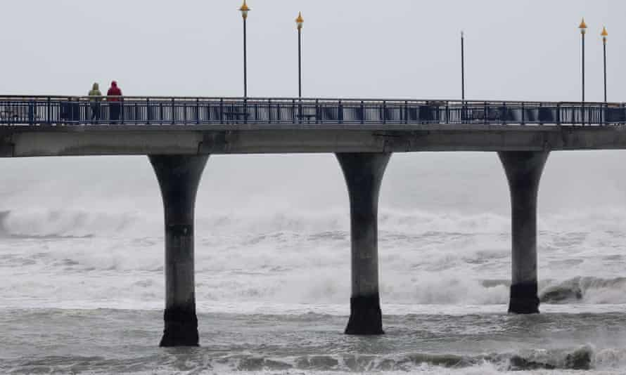 A couple walk on New Brighton pier as heavy rain continues in the city of Christchurch on May 31, 2021, after the area was pounded by heavy rains that forced authorities to declare a state of emergency in the province of Canterbury. (Photo by Sanka VIDANAGAMA / AFP) (Photo by SANKA VIDANAGAMA/AFP via Getty Images)
