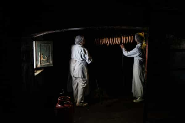 Workers hang hand-made chorizos in the farm's traditional smoke room
