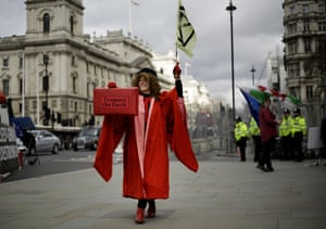 An Extinction Rebellion protester with a red box labelled 'Treasure the Earth'