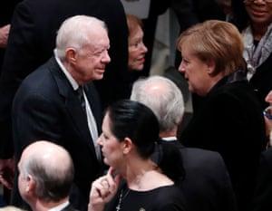 Former US president Jimmy Carter talks with German chancellor Angela Merkel.
