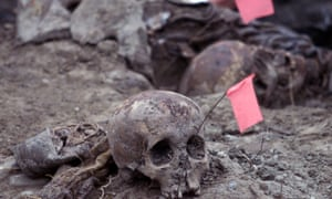Forensic experts uncover remains found in a mass grave