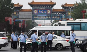Chinese police guard the entrance to the closed Xinfadi meat market in Beijing on 13 June 2020. Eleven residential estates in south Beijing have been locked down due to a fresh cluster of coronavirus cases linked to the market