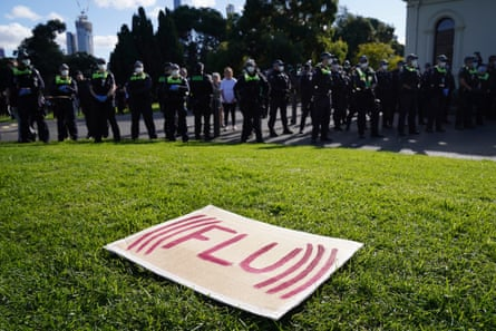 A sign reading (((FLU))) sits on the grass in front of police and protesters