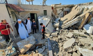 People inspect damage from a rocket attack by forces loyal to the Libyan strongman Khalifa Haftar in a residential area of Tripoli.