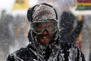 Snow swirls around a demonstrator in goggles.