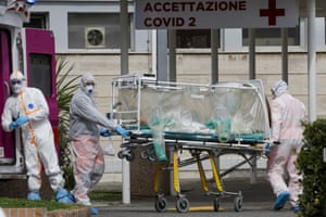 A patient in a biocontainment unit is carried on a stretcher from an ambulance into the Columbus Covid 2 hospital in Rome.
