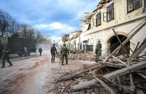 Soldiers stand next to wreckage and damaged buildings in Petrinja after the town was hit by an earthquake.