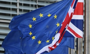 A union flag hangs next to European Union flags fluttering in front of the European commission building,