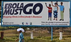 A man walks past an Ebola campaign banner in 2015