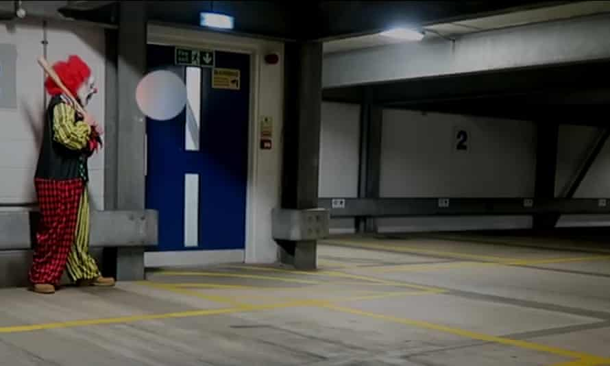 Videograb from CCTV from a car park in Kent shows a man dressed as a clown preparing for a prank.
