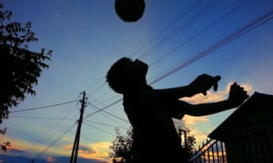 A boy heading a ball in silhouette against a dusk sky