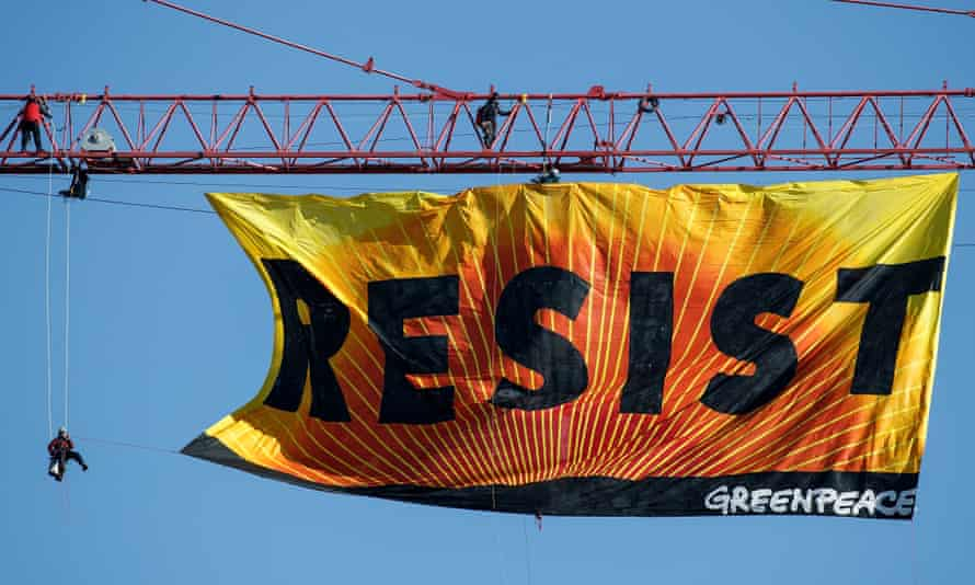Greenpeace protesters Climb Atop A Crane In Washington, D.C to unfurl a banner that reads Resist