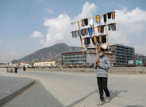 An Afghan boy holds protective face masks for sale in downtown.