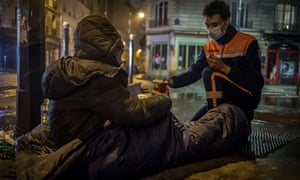 A French Civil Protection volunteer serves a coffee to a homeless man in the streets of Paris, France 10 March 2021. French Civil Protection roamed to meet the homeless to distribute food and basic necessities since the start of the coronavirus pandemic, which has worsened the situation of people living in the streets.