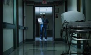 Medical professional reading medical chart in hospital corridor