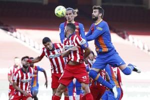 Barcelona's Antoine Griezmann (top left) and Gerard Pique go up for a header