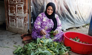 A Syrian woman prepares vegetables in a refugee camp