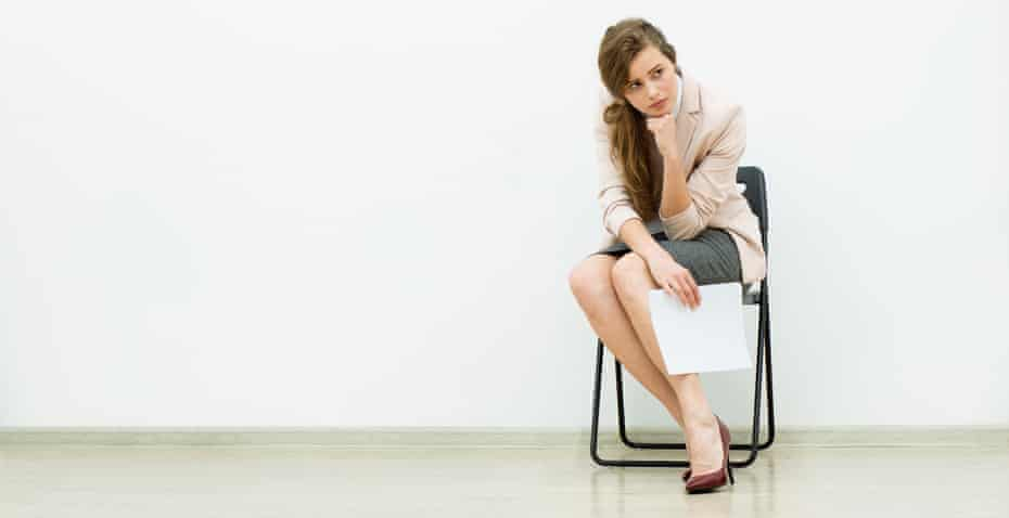 woman in office outfit sitting in a chair with some sheets of paper in hand and thinkingFHHKCN woman in office outfit sitting in a chair with some sheets of paper in hand and thinking