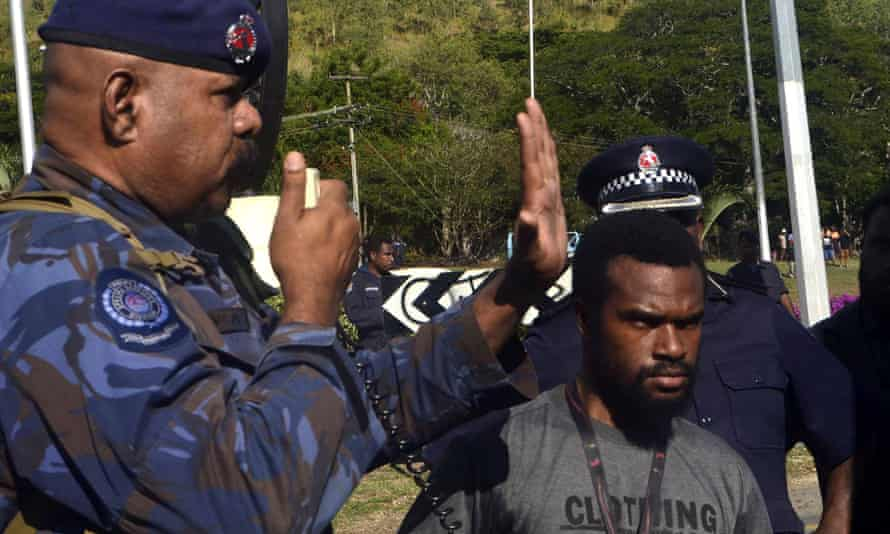 A police officer gestures to students in Port Moresby