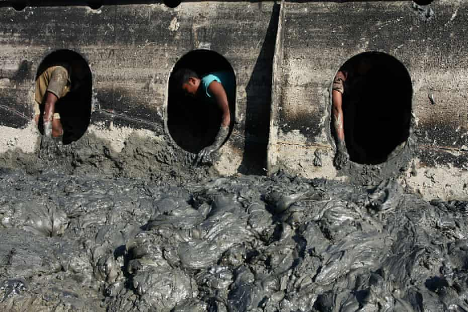 Labourers seen through portholes of a freighter.