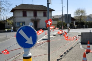 This picture taken on April 5, 2020 shows a border between Switzerland and France closed by concrete blocks and adorned with Swiss flags in Presinge near Geneva as the country remains in lockdown to curb the spread of the novel corona virus, COVID-19.