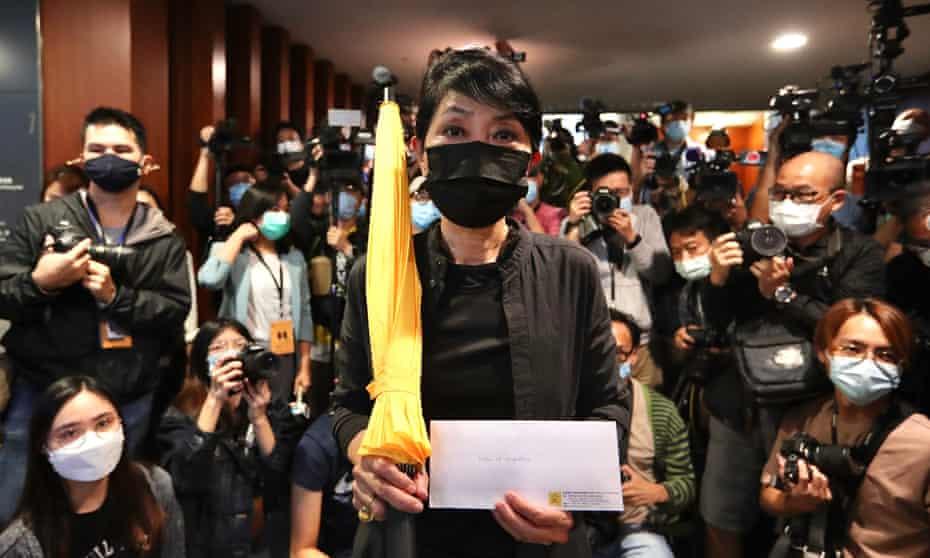 Legislator Claudia Mo with a protester's symbolic umbrella and her resignation letter last week.