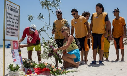 People lay flowers on the beach near the Imperial Marhaba hotel, the site of a mass shooting on 26 June 2015.