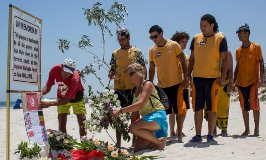 Tourists and hotel staff place flowers at a memorial sign on the beach where the attacks took place.