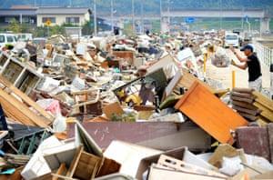 A man leaves debris at a collection point in Mabicho area in Kurashiki, Okayama