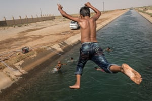 Children jump into a small tributary of the Euphrates river