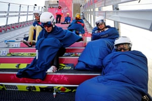 Ski jumpers wrap up warm prior to setting off during practice.