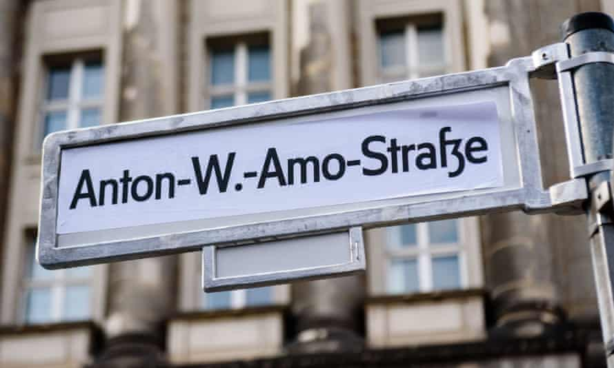 A sticker reading Anton-W-Amo-Straße covers a Mohrenstraße sign in Berlin.
