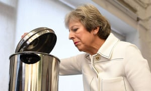 Theresa May peers into a hot water urn on a visit to a social group