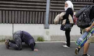 A man kneels on the ground after Slovenian police let him cross the border at Rigonce.