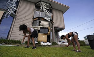 Shards of glass from broken windows are gathered up in the aftermath of Hurricane Ida, in Houma, La.