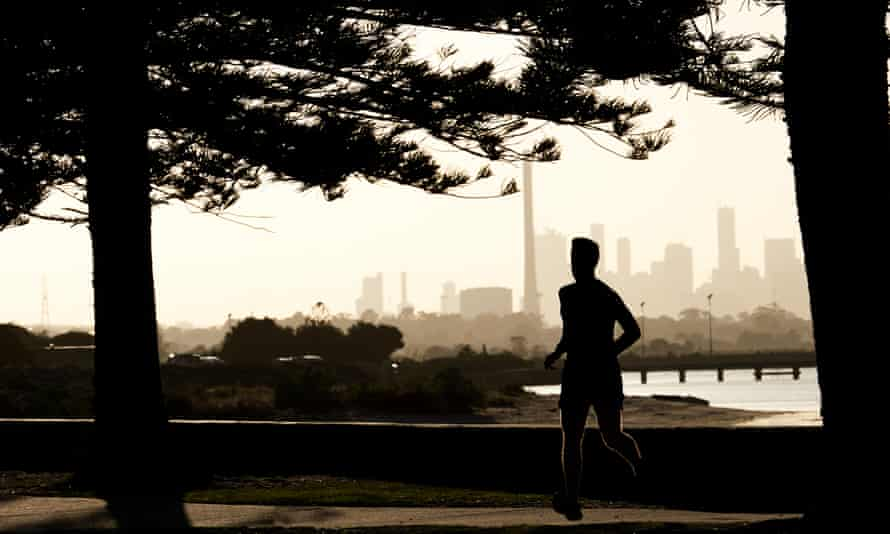 Early morning male jogger silhouetted against the skyline of the city of Melbourne, Australia.