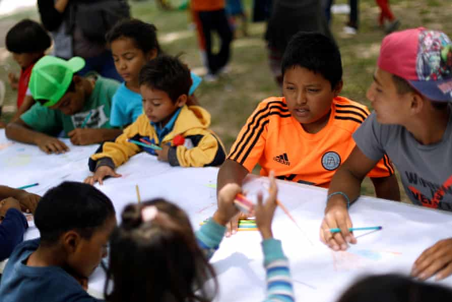 Cristopher 11, from El Salvador, travelling with a caravan through Mexico, draws at an improvised shelter, in Irapuato, Guanajuato State, 16 April