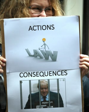 A protester holds a sign showing Boris Johnson in jail